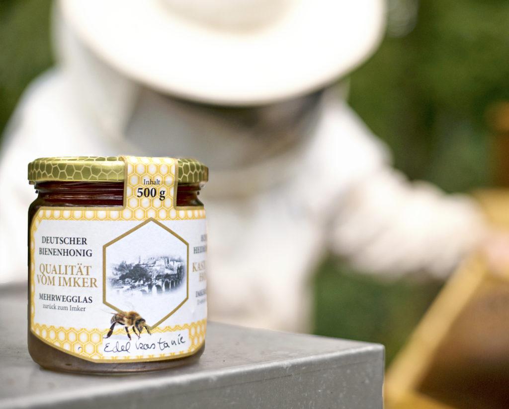 Honigglas mit Imker im Hintergrund
