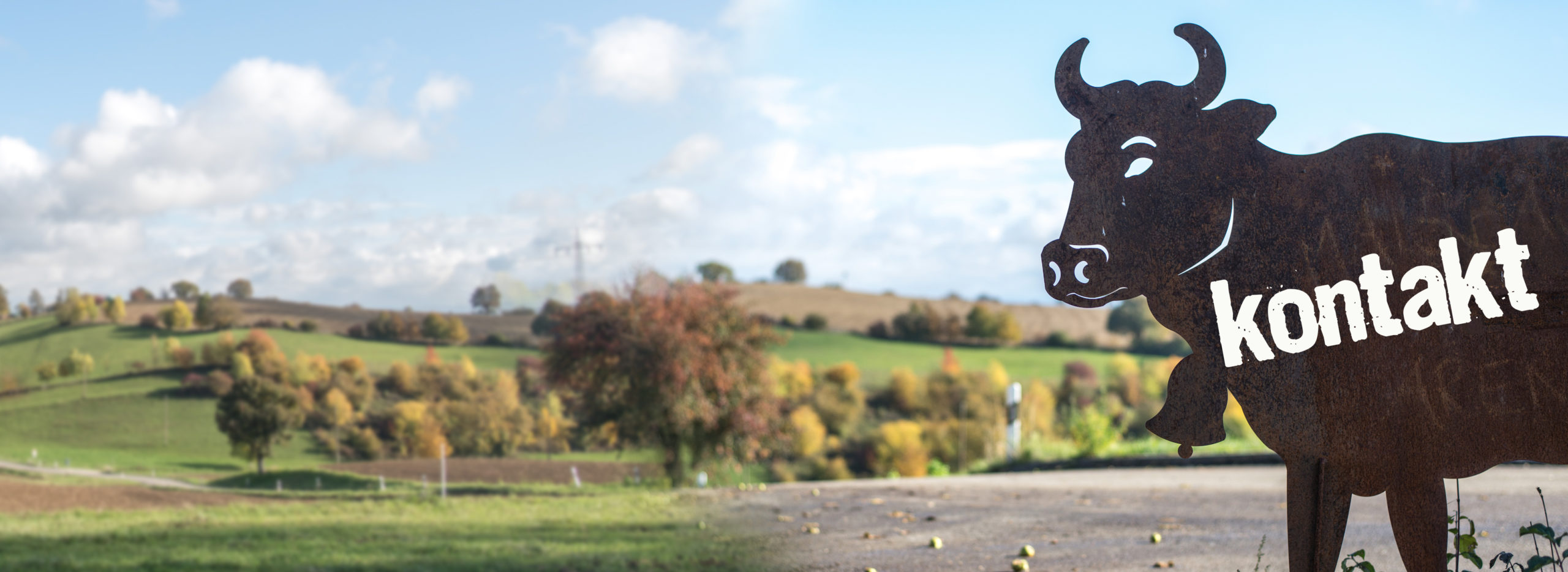 Eine Kuh aus Eisen mit dem Wort Kontakt steht vor einer idyllischen Landschaft