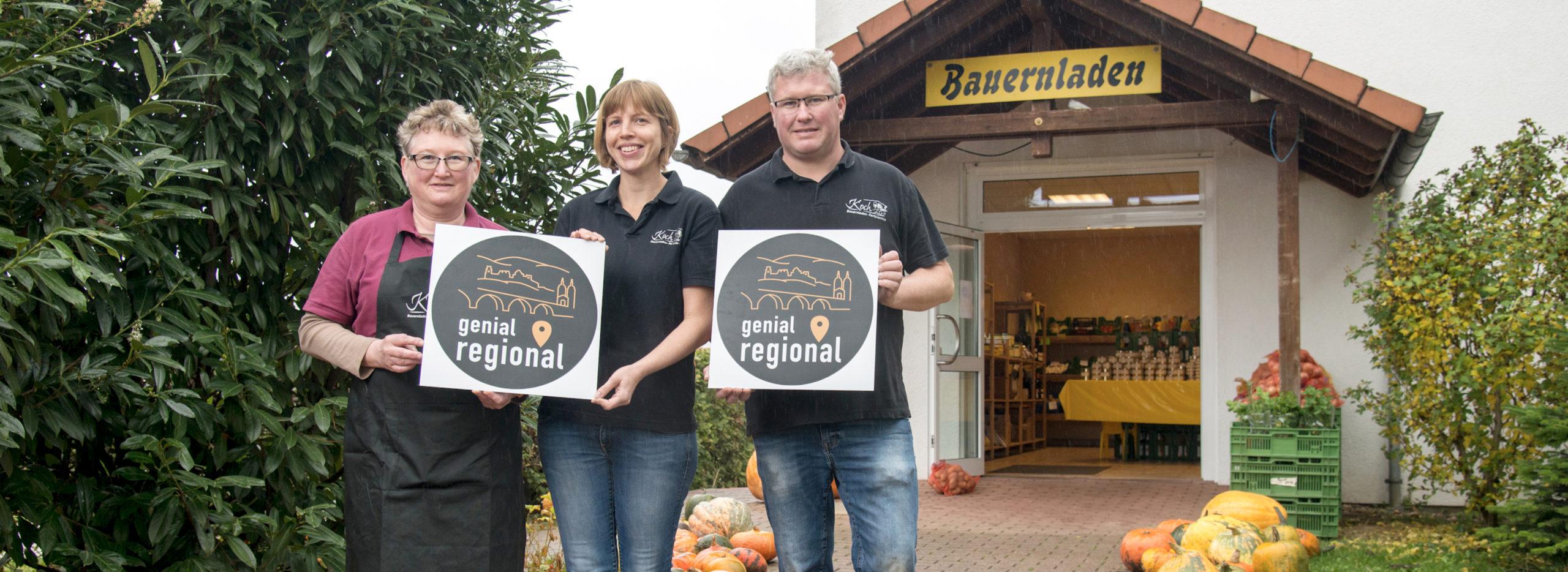 Familie Koch steht mit Genial regional Label vor ihrem Bauernladen