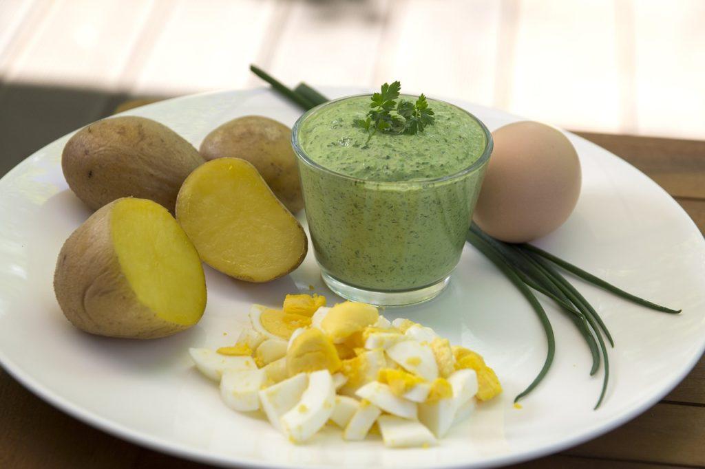 Teller mit Kartoffel, hartgekochten Eiern, Schnittlauch und einem Glas Grüne Soße