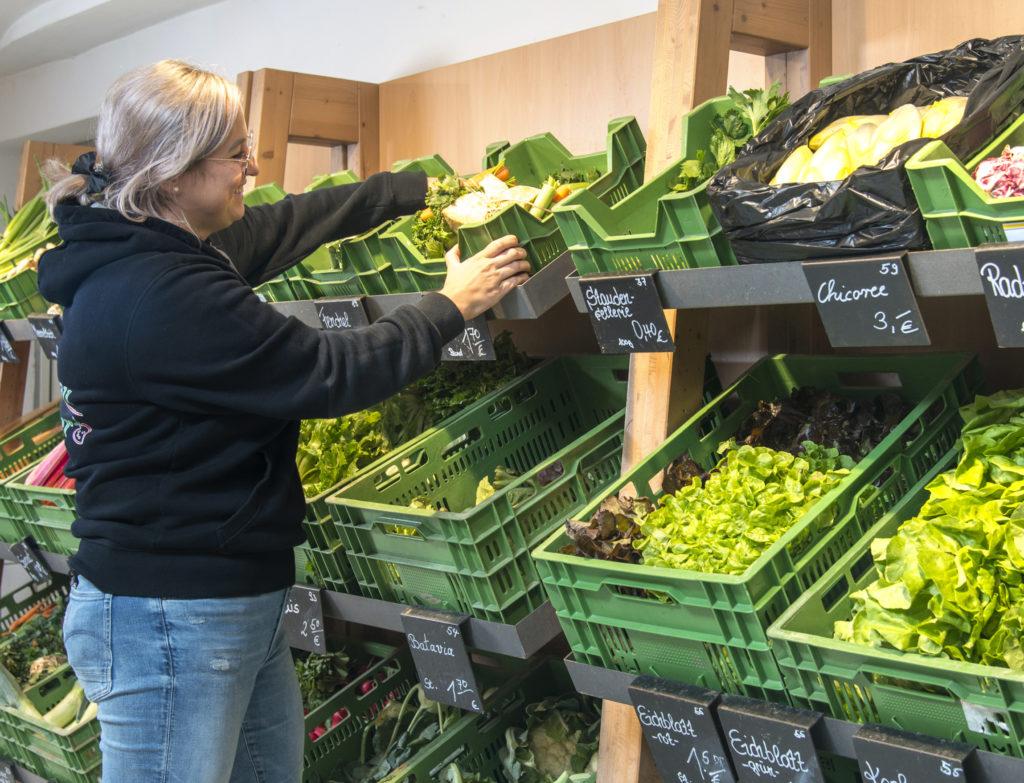 Frau sortiert Gemüse ein und steht vor Regal mit Obst und Gemüse