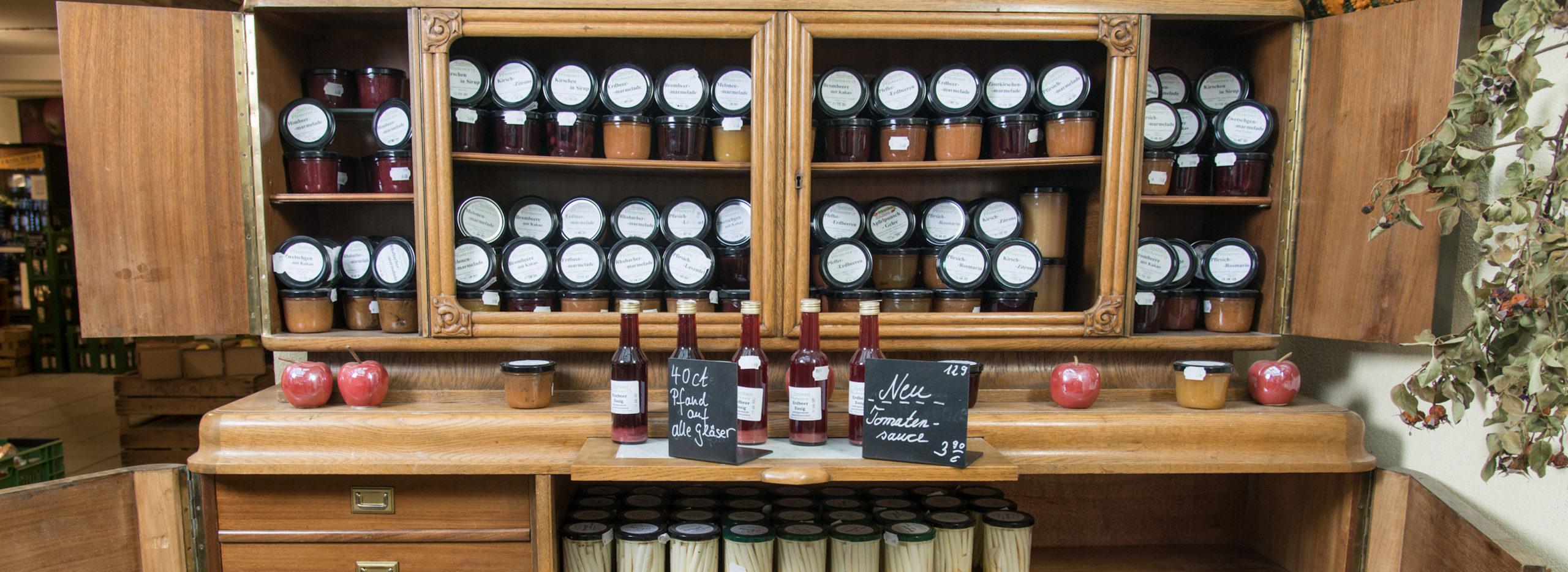 Holzschrank mit hausgemachten Produkten wie Marmeladen Spargel oder Tomatensauce