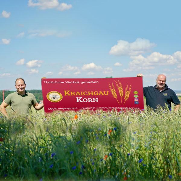 Mitglieder von KraichgauKorn im Feld mit Werbeschild
