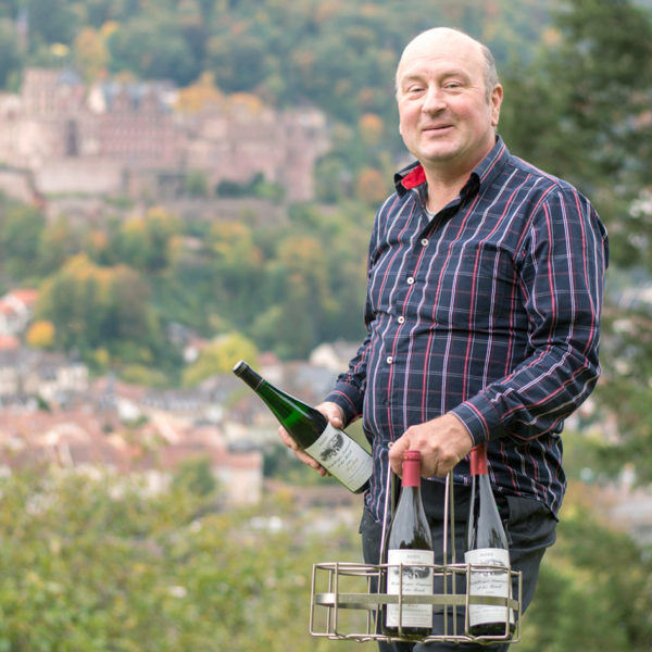 Winzer Spies im Weinberg mit Heidelberger Schloss im Hintergrund