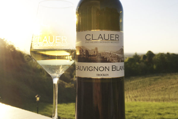Flasche Gutswein mit Glas im Sonnenlicht von Weingut Clauer